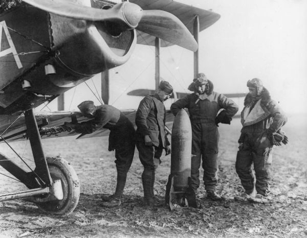 Aircrew of 27 Squadron RAF examine a 230lb bomb while an Air Mechanic checks the bomb carrier under the wing