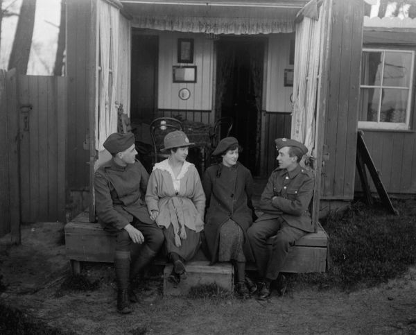 Charles Brown (right) in Army uniform, chatting with friends or relatives, circa 1919