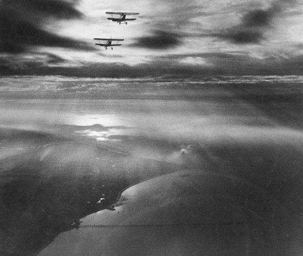 Hawker Fury aircraft over Southend. This photograph is in the style of Alfred Buckham
