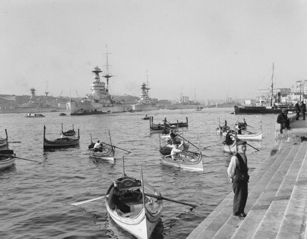Dhaisas in Grand Harbour, with warships of the Royal Navy in the background, Malta 1935