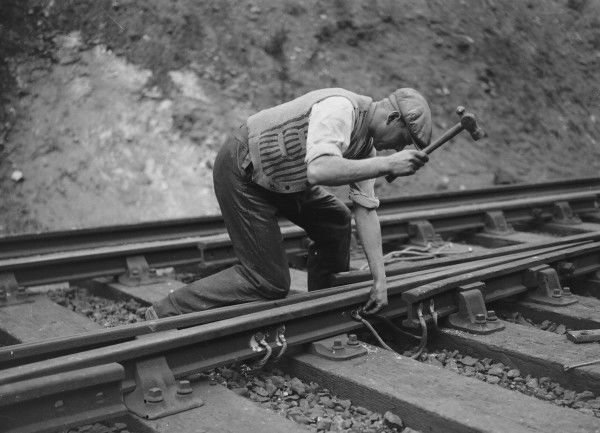 A workman attaching wiring to the rails