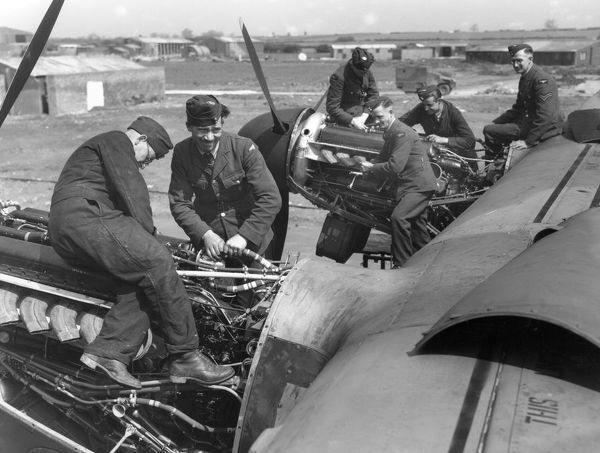Avro Lancaster I on ground, engine fitters of 207 Squadron at work on starboard engines, RAF Bottesford, 1942