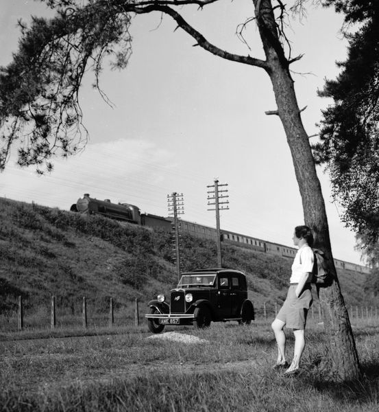 A rambler pauses while she is overtaken by a motorist in an Austin Six saloon and a Southern Railway express train on the embankment