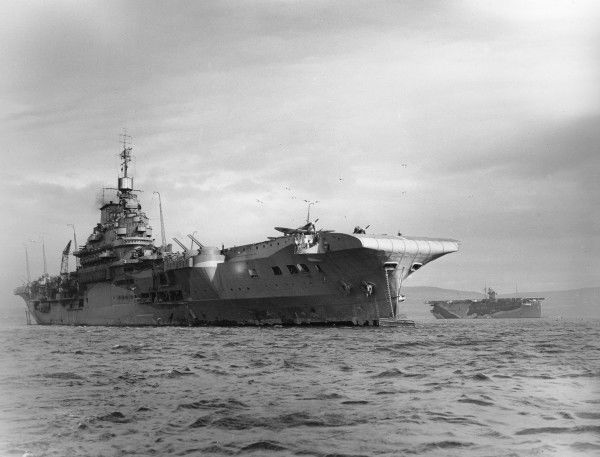 HMS Indomitable at its moorings with another aircraft carrier in the distance