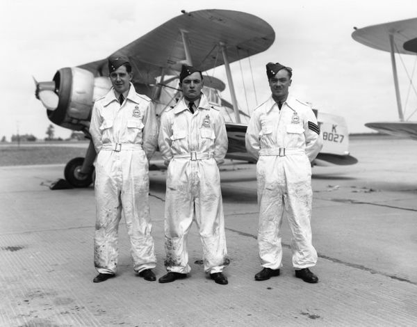 Pilot Officer R L Lorimer, Flying Officer G H J Feeny and Sergeant Thomas Dewdney of 87 Squadron, standing in front of a Gloster Gladiator at RAF Debden, 1938