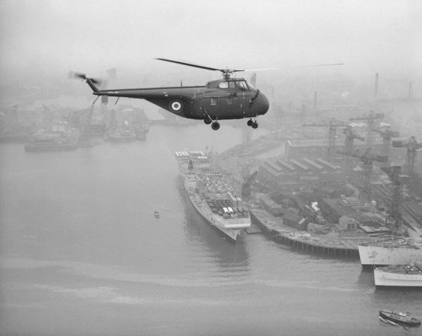 Sikorsky Whirlwind HAS.22 (WV192) flying over HMS Perseus which is loaded with vehicles and aircraft for overseas, 1953. The helicopter still displays part of its US Navy markings