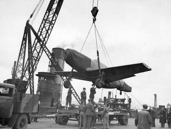 P-51 Mustang aircraft being transferred from floating crane to special carrier beam fitted to a 8-wheel trailer