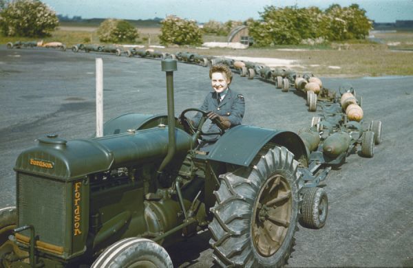 A WAAF tractor driver with a train of full bomb trolleys, RAF Mildenhall 1942